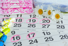 Woman hygiene protection , calendar close up.menstruation with cotton swabs , white daisies, Sanitary napkins on a light backgroun Royalty Free Stock Images