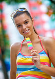 Woman with ice cream. Young woman eating colorful ice cream Royalty Free Stock Photo