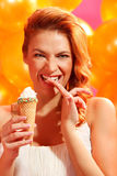 Woman with ice cream. Portrait of happy young woman tasting ice cream over balloons Royalty Free Stock Photography