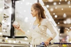 Woman with ice cream at grocery store freezer Royalty Free Stock Photography