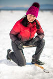 Woman ice-fishing in the winter Stock Photos