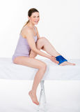 Woman with ice pack on ankle. On white background stock photo