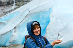 Woman with ice piece near Nigardsbreen glacier (Norway) Stock Image