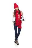 Woman with ice skates. Full length of smiling young woman wearing warm hat and scarf carrying a pair of ice skates, over white background Stock Images