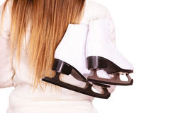Woman with ice skates getting ready for ice skating. Woman carrying a pair of ice skates getting ready for ice skating, winter sport activity. Back view isolated Royalty Free Stock Photo