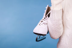 Woman with ice skates getting ready for ice skating. Woman carrying a pair of ice skates getting ready for ice skating, winter sport activity, on blue Royalty Free Stock Photography