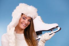 Woman with ice skates getting ready for ice skating. Winter sport activity. Smiling girl wearing warm clothing sweater and fur cap on blue studio shot Stock Image