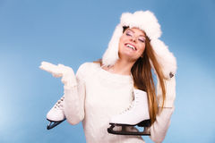 Woman with ice skates getting ready for ice skating. Winter sport activity. Smiling girl wearing warm clothing sweater and fur cap on blue studio shot Royalty Free Stock Photography
