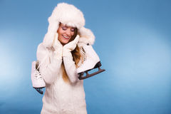 Woman with ice skates getting ready for ice skating. Winter sport activity. Smiling girl wearing warm clothing sweater and fur cap on blue studio shot Stock Images