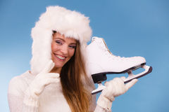 Woman with ice skates getting ready for ice skating. Winter sport activity. Smiling girl wearing warm clothing sweater and fur cap on blue studio shot Royalty Free Stock Photos