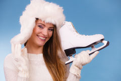 Woman with ice skates getting ready for ice skating. Winter sport activity. Smiling girl wearing warm clothing sweater and fur cap on blue studio shot Stock Photos