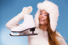Woman with ice skates getting ready for ice skating. Winter sport activity. Smiling girl wearing warm clothing sweater and fur cap on blue studio shot Royalty Free Stock Images