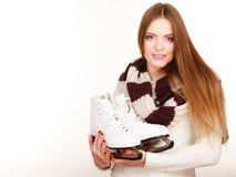 Woman with ice skates getting ready for ice skating. Winter sport activity. Smiling girl wearing warm clothing on white studio shot Royalty Free Stock Image
