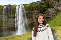 Woman in Icelandic sweater by waterfall on Iceland Royalty Free Stock Photos
