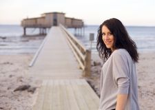 Woman on an Idyllic Beach Facing the Camera. Against the house over the water as background Royalty Free Stock Images
