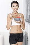 Woman ieating fruit in fitness clothes Stock Photography