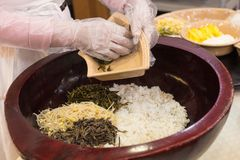 A woman if preparing a korean traditional food. A woman wearing a pair of gloves is preparing a Korean  traditional food using a maroon coloured pot stock photography