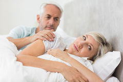 Woman ignoring mature man in bed Stock Images