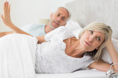 Woman ignoring mature man while lying in bed Royalty Free Stock Photo