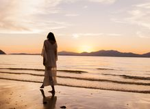 Woman iIn White Dress Walking On Beach royalty free stock images