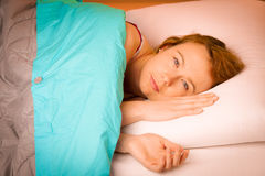 Woman iling on pillow in bed, covered with blanket Royalty Free Stock Photo