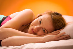 Woman iling on pillow in bed, covered with blanket Stock Photo