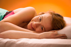 Woman iling on pillow in bed, covered with blanket Royalty Free Stock Photography