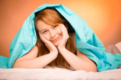 Woman iling on pillow in bed, covered with blanket Stock Photos