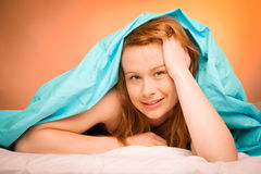 Woman iling on pillow in bed, covered with blanket Royalty Free Stock Photos