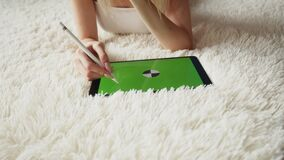 Woman illustrator lies on carpet and draws with stylus on graphic tablet with chromakey screen, front view. Woman artist