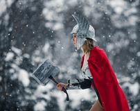 Woman in image of Germanic-Scandinavian God of thunder and storm goes with hammer in her hand. Cosplay. royalty free stock photography