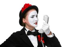 Woman in the image mime holding a handset. Business woman as mime holding a handset and with hatred looking to the phone, isolated on white background. Concept Stock Photos