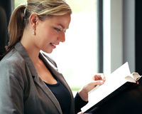Woman immersed in a book. Profile of a beautiful blonde woman immersed in reading a book with a small smile of pleasure on her lips Royalty Free Stock Photo