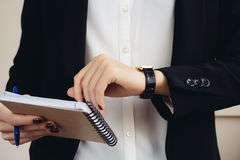 Free Woman In A Business Suit Holding A Notebook And Looks At Her Watch Stock Images - 62097084