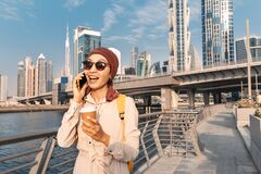 Free Woman In A Headscarf Drinking Coffee And Talks And Gossips On The Phone With A Friend On The Dubai Walk Canal Royalty Free Stock Images - 221589829