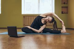 Free Woman In Black Sportswear Does Yoga, Performs Online Exercise Parivritta Janu Shirshasana, Looks Into A Laptop Royalty Free Stock Photo - 216718645
