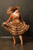 Woman In Brown Dress Dancing Next To The Wall Stock Images