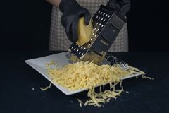 Free Woman In Checkered Apron Rubs Cheese On A Grater. Home Cooking. Adjarian Khachapuri Recipe – Georgian Cheese Bread Royalty Free Stock Images - 191760449
