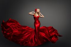 Free Woman In Fluttering Red Dress, Waving Silk Cloth, Artistic Fashion Model In Flowing Silk Fabric Stock Image - 179748271