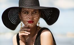 Free Woman In Hat Portrait. Fashion Luxury Model In Black Summer Hat With Make Up And Golden Jewelry. Close Up Beauty Face Over Sky Royalty Free Stock Images - 215398169
