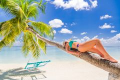 Free Woman In Hot Sunny Weather Laying Down On A Palm Tree And Enjoying Tropical Beach Vacation, Carefree Holiday Stock Image - 139260041
