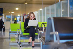 Woman In International Airport Terminal, Working On Her Laptop Royalty Free Stock Photography