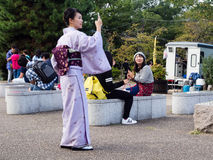Woman In Kimono Taking Pictures With Cellphone Royalty Free Stock Photography
