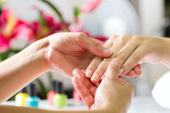 Free Woman In Nail Salon Receiving Hand Massage Stock Photography - 26869222