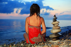 Woman In Red Sitting Near To Pyramid From Pebble Royalty Free Stock Photo