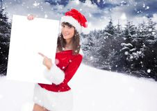 Free Woman In Santa Hat Pointing At Blank Placard Royalty Free Stock Photo - 81443005