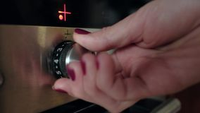 Woman includes a cooking stove. Close up of female hand turning on the oven in modern kitchen stock video