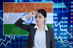 Woman with Indian flag and declining chart. Image of frustrated businesswoman standing in front of declining financial graph and Indian flag Royalty Free Stock Image