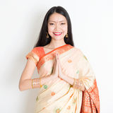 Woman with Indian greeting pose. Portrait of mixed race Indian Chinese girl with traditional sari dress in greeting gesture, standing on plain background Stock Image