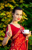 Woman in Indian sari with cup of tea. Beautiful woman in Indian red sari with cup of tea gesturing mudra outdoors stock photography